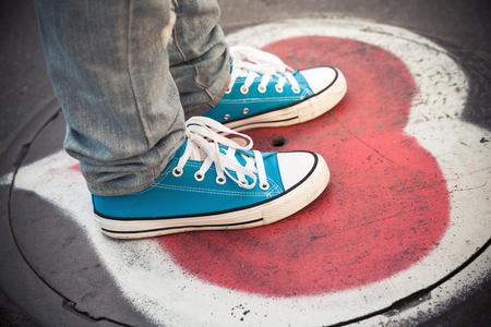 pieds sales: espadrilles bleues, adolescent pieds debout sur regard d'égout urbain avec coeur soupir