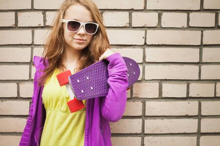 tonal: Blond teenage girl in sunglasses with skateboard near gray urban brick wall, vintage tonal correction, old style filter effect