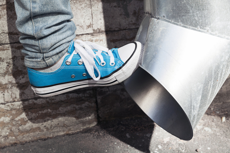 aggression: Teenager in blue sneakers kicks drainpipe, aggression concept