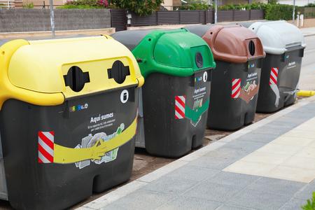 separacion de basura: Calafell, España - 22 de de agosto de 2014: envases de plástico de colores en una fila para la recolección de basura separada