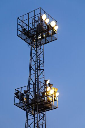 ferm: Industrial light mast with glowing lamps on dark blue sky background