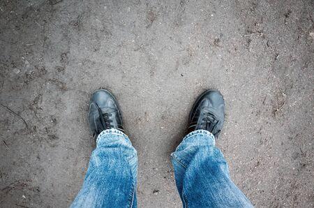 pieds sales: pieds m�les en jean bleu et des chaussures noires, debout sur une route rurale sale, vue premi�re personne Banque d'images