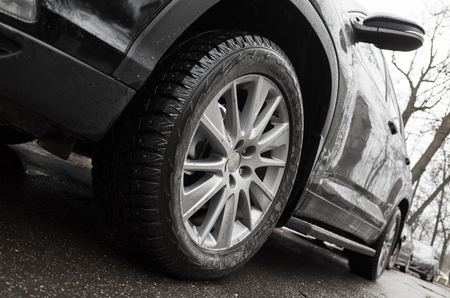 Closeup wide angle photo fragment of black car, light alloy wheel with winter tires on dirty city road. Selective focus and shallow DOF Stock Photo