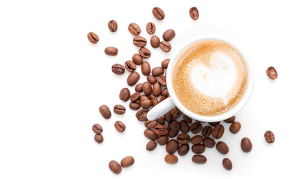 capuchino: Pequeña taza de capuchino con los granos de café y el corazón en forma de espuma de leche, vista desde arriba aislados en fondo blanco Foto de archivo