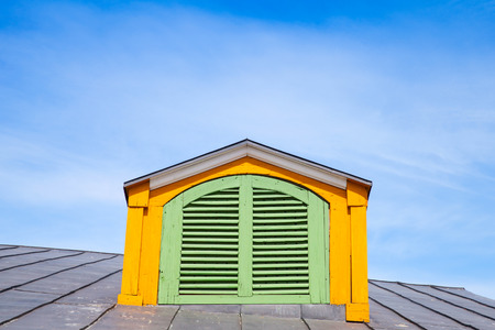attic window: Yellow wooden attic window with closed green shutters