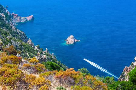 sud: Coastal landscape of South Corsica. Fast motor boat goes along Capo Rosso, Piana region Stock Photo