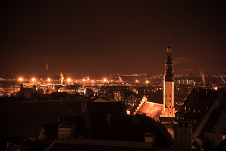 spire: Cityscape of old Tallinn at night, Holy Spirit Church spire with illumination. Warm tonal correction photo filter effect