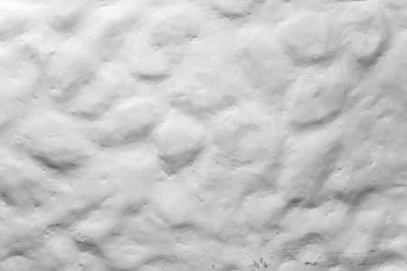 Rough uneven white painted stone wall, closeup background photo texture