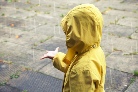 Little child in yellow raincoat playing with raindrops. Vintage stylized tonal correction photo filter effect Stock Photo