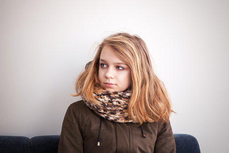 outwear: Beautiful blond Caucasian teenage girl in warm outwear sitting on blue sofa over white wall Stock Photo