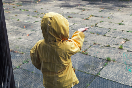 tonal: Little child in yellow raincoat playing with raindrops. Vintage tonal correction photo filter effect