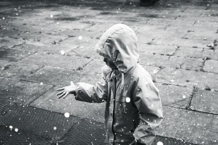 Małe dziecko w płaszczu grając z kroplami deszczu. Stylizowane zdjęcie monochromatyczne