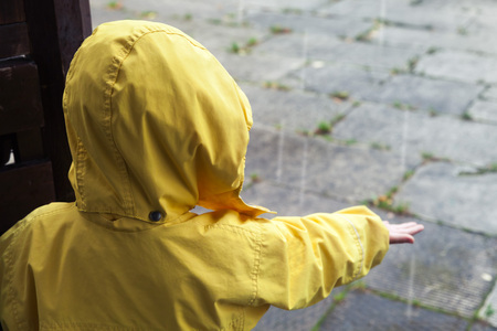 rain wet: Little child in yellow raincoat playing with rain water drops