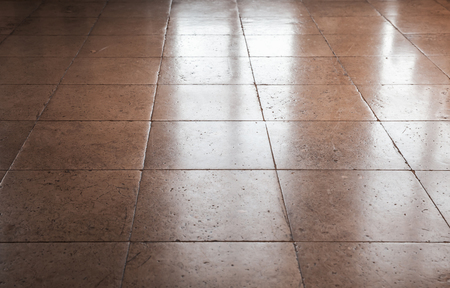 tiling: Shining brown stone floor tiling, background texture with perspective effect