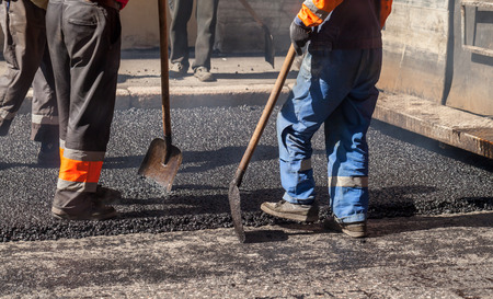 asphalting: Urban road under construction, asphalting in progress, workers in uniform with shovels