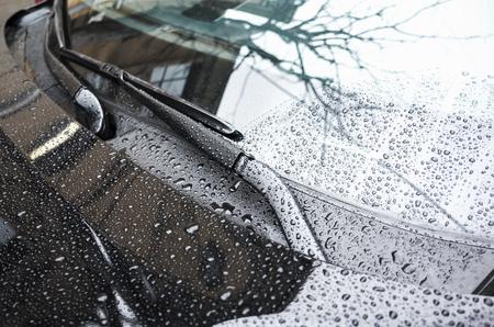 それを雨滴、セレクティブ フォーカスと浅いクローズ アップ写真で黒い車フード フラグメントとフロント ガラス ワイパー
