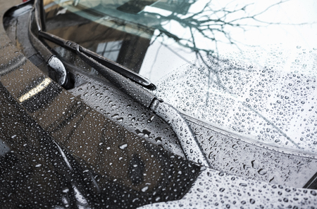 Black car hood fragment and windshield wipers with raindrops on it, closeup photo with selective focus and shallow DOF