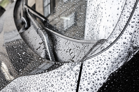 Black metallic glanzende auto motorkap fragment en ruitenwissers met regendruppels op het, close-up foto met selectieve aandacht en ondiepe DOF