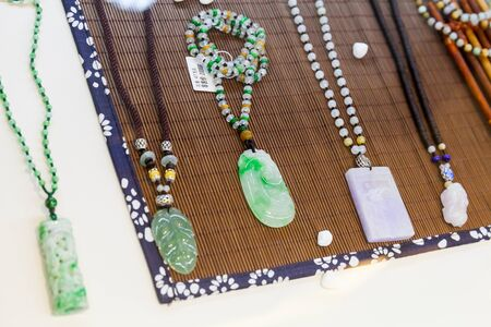 green gemstones: Hangzhou, China - December 2, 2014: Traditional Chinese stone amulets made of green and blue jade lay on the counter in gemstones shop