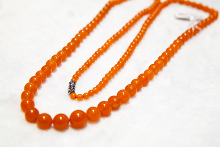 necklace: Chinese necklace made of red round agate stones lays on white counter