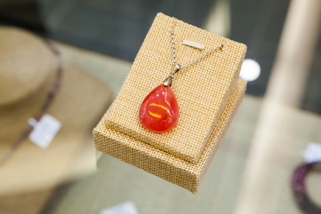feng shui: Chinese stone amulet made of red agate lays on a glass counter Stock Photo