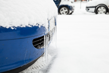 Icicles hanging on the car bumper covered with snow Stock Photo