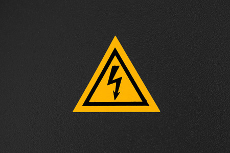 standard steel: High voltage triangle warning sign mounted on black metal wall Stock Photo