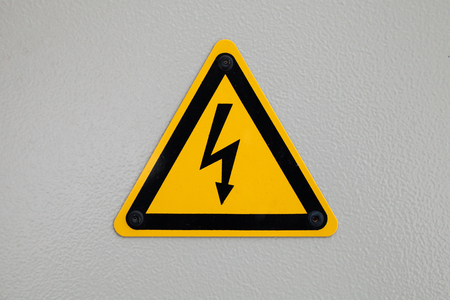transformator: High voltage triangle warning sign mounted on gray metal wall