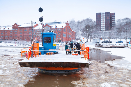 turku: Turku, Finland - January 17, 2016: Ordinary passengers of Fori, light traffic ferry that has served the Aura River for over a hundred years, first taking passengers in 1904