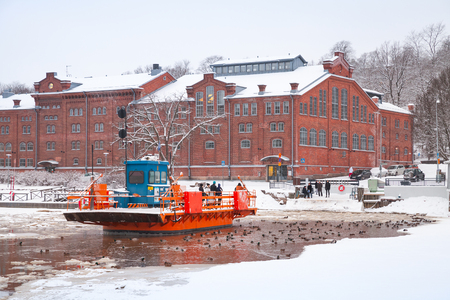 17 years: Turku, Finland - January 17, 2016: Ordinary people go on city boat Fori, light traffic ferry that has served the Aura River for over a hundred years, first taking passengers in 1904