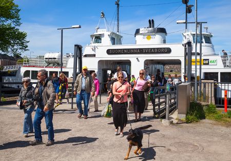 descend: Helsinki, Finland - June 13, 2015: Tourists descend from the Suokki ship to the pier. This ferry travels from Helsinki to Suomenlinna island and back
