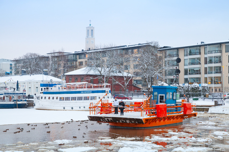 turku: Turku, Finland - January 17, 2016: Ordinary passengers on historic city boat Fori, light traffic ferry that has served the Aura River for over a hundred years, first taking passengers in 1904