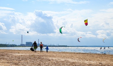 kiter: Sosnovy Bor, Russia - July 19, 2015: Family walking on the beach. Kitesurfers ride the waves of the Gulf of Finland near the Leningrad Nuclear Power Plant