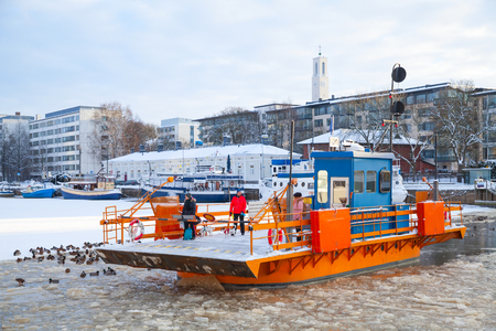 ferryboat: Turku, Finland - January 22, 2016: Ordinary passengers go on city boat Fori, light traffic ferry that has served the Aura River for over a hundred years Editorial
