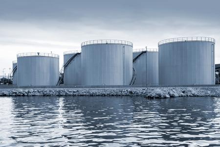 Shining oil tanks on the sea coast in Varna port, Bulgaria. Blue toned photo 스톡 콘텐츠