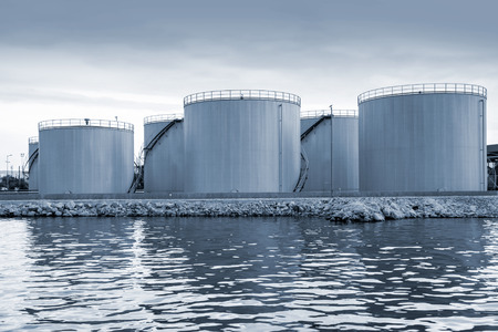 Shining oil tanks on the sea coast in Varna port, Bulgaria. Blue toned photo Banque d'images
