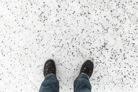 anti season: Male feet in blue jeans and black shoes standing on snowy winter road with anti-slip granite chippings, first person view Stock Photo