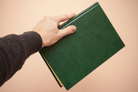 tonal: Book with empty dark green leather cover in male hand, retro style warm tonal correction photo filter effect Stock Photo