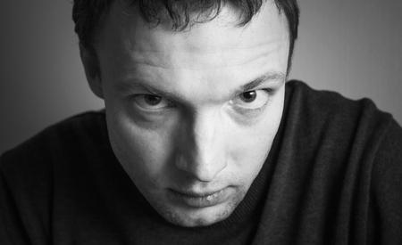 smart man: Young serious Caucasian man, close-up studio portrait, black and white photo Stock Photo