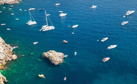 motorboats: Mediterranean seascape, bird eye view. Pleasure yachts and motorboats moored near coastal rocks Stock Photo