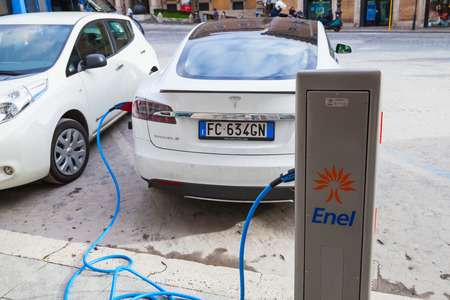 recharging: Rome, Italy - February 13, 2016 : White Tesla model S car charging at the EV public recharging station in the city of Rome, back view