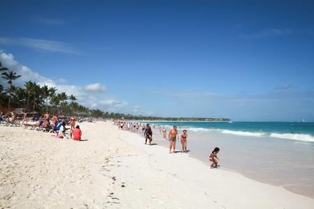 cana: Punta Cana, Dominican republic - January 14, 2015: Coastal Caribbean seascape. Atlantic ocean coast, ordinary tourists walk along sandy beach of Punta Cana resort