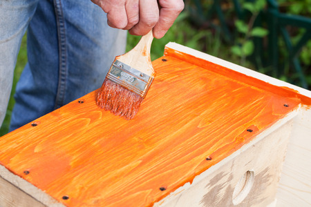 adds: Homemade birdhouse made of wood is under construction, worker adds red protective covering with brush