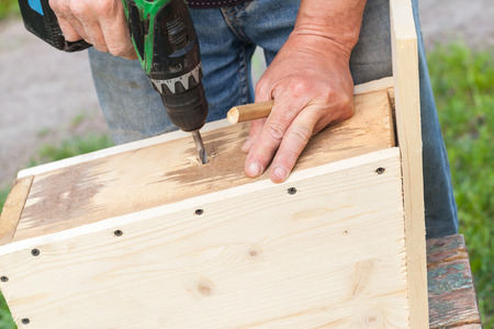 Homemade birdhouse made of wood under construction, carpenter works with drill, closeup photo