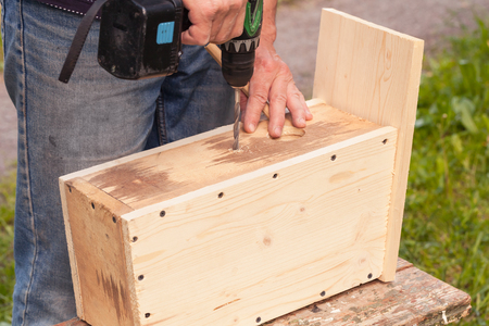 chippy: Homemade birdhouse made of wood is under construction, carpenter works with drill Stock Photo