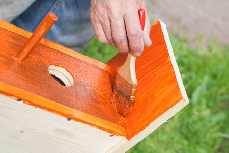 adds: Homemade birdhouse made of wood is under construction, worker adds protective covering with brush Stock Photo