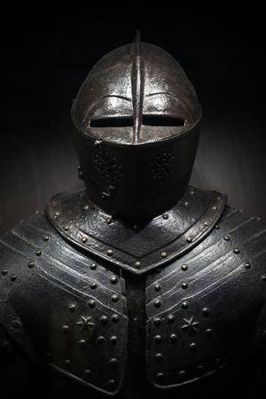 中世の騎士の古代金属鎧。縦の写真を暗い