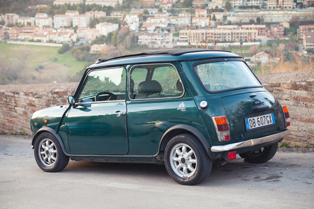 mk: Fermo, Italy - February 8, 2016: Dark green Austin Mini Cooper Mk III rear view. This modification of Mini is a small economy car made by the British Motor Corporation between 1969 and 1976 Editorial