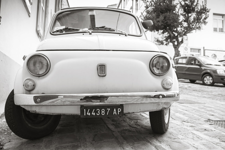 black history: Fermo, Italy - February 11, 2016: Old white fiat 500 L city car on the street of Italian town, close-up front view, monochrome photo Editorial