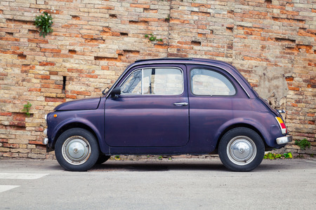 used car: Fermo, Italy - February 11, 2016: Old Fiat Nuova 500 city car produced by the Italian manufacturer Fiat between 1957 and 1975 stands in a town, side view